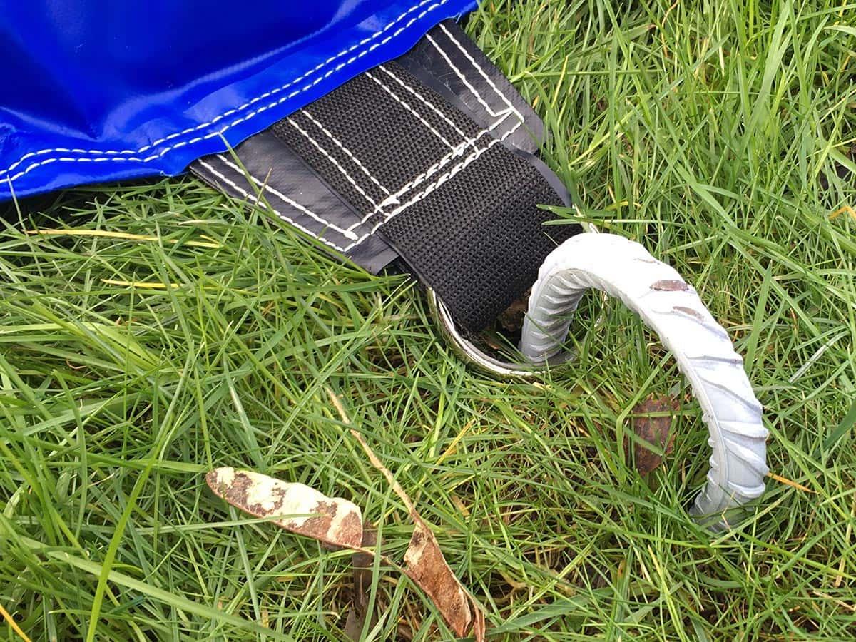 Mit den Erdnägeln die Hüpfburg am Boden fixieren. Den Teppich vor den Eingang legen